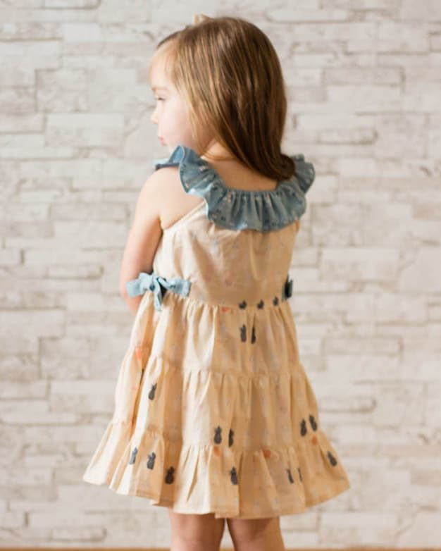 Sandy's ruffle neck tiered top and dress is just darling for all ages. Featuring a ruffle elastic neckline, it is a great summer dress pattern. Choose top or dress length. This pattern also has optional side ties to cinch in the waist and add a beautiful feminine touch. There are no closures on this dress so it is perfect for dressing up or everyday play. Want the ultimate twirl factor? Choose the tiered skirt option. This pattern is great for showcasing all your favorite prints in one dress. the simple life pattern company. pdf downloadable beginner sewing patterns. dress top skirt knit woven summer spring fall winter sleeves modern toddler girl kids fashion trendy vintage fast easy pattern strappy back open back flounce b