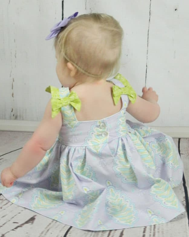 "Simple Life Pattern Company Saylor's Squared Bow Back Top & Dress. Saylor's Squared Bow Back Top & dress has such a fun and modern look as a top or dress.   Baby Saylor features an open squared back with side bows or large center bow, square cutout back with side bows or simple square back.   Taylor can be made with the sweetest sleeve tabs or sleeveless.  The higher bodice is perfect for adding embellishments or monograms.  Saylor also features a simple skirt with a deep hem or ruffle skirt. Top version only has simple skirt option but the dress features both versions. Square back fancy play dress holidays baby newborn pdf sewing pattern bows sleeve tabs ruffle skirt summer spring trendy modern bonus hair bow tutorial 2"" bows 3"" bows 5"" bows"