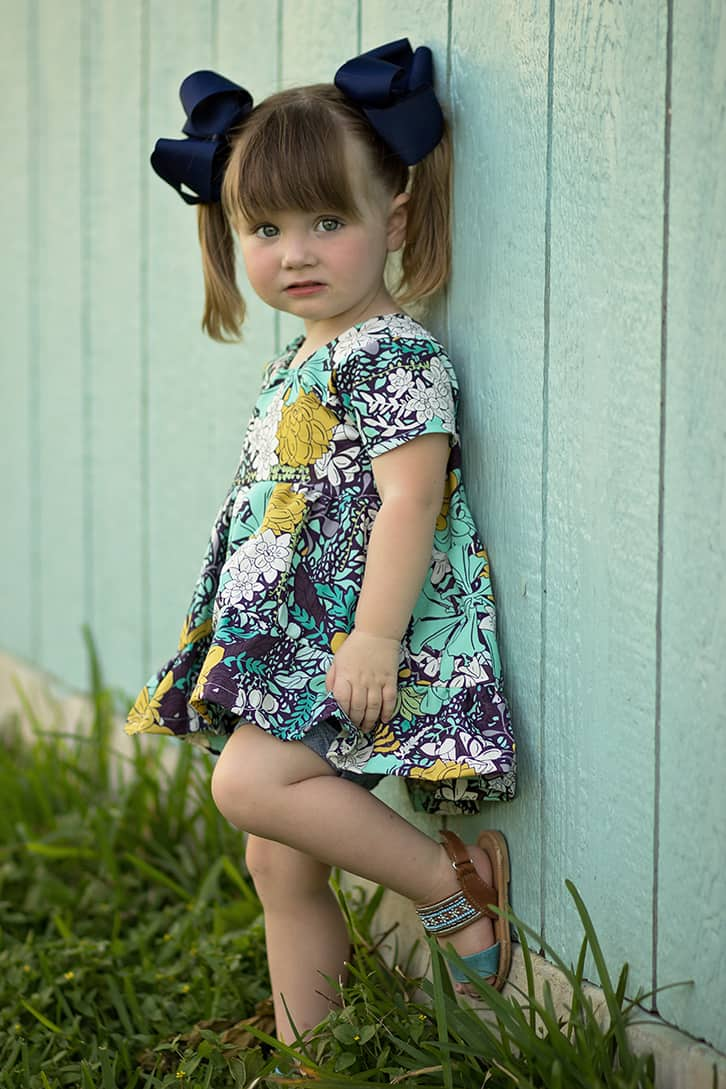Simple Life Pattern Company | Patricia's Boho Top & Dress Downloadable PDF Sewing Pattern Girls and Toddler Sizes 2t-12 Pattern of the month Patricia's is packed full of options. Starting with Top or dress length. It also has a tank version, short sleeves, bell sleeves and long sleeves. You can choose between the moderate high low hem or the dramatic high low hem. Patricia can be made in knit or woven's and is very flattering in lightweight flowy types of fabrics such as voile or rayon. The back features a slight scoop back and has NO closures – just slides on over the child's head. Plenty of playing room without being boxy or too baggy. You will love how many looks you can achieve with just this pattern! And how quickly you can sew these up!