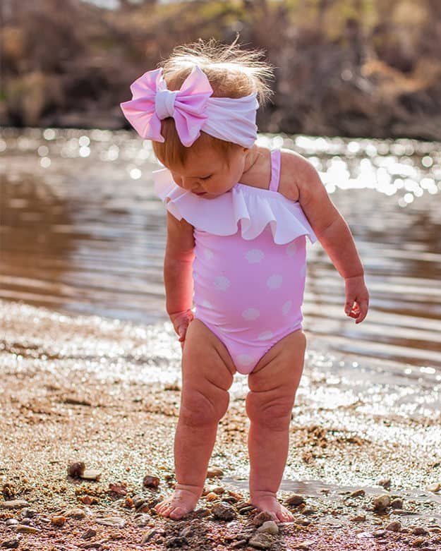 Simple Life Pattern Company | Baby Elise's One Shoulder Swimsuit & Tankini. Downloadable PDF Sewing Pattern for Baby Sizes Newborn to 24 Months. Baby Elise's One Shoulder swimsuit can be sewn as a one piece or a tankini.  Both versions can feature the optional flounce and skinny strap or be left as a simple single shoulder suit.  The tankini also has an optional circle skirt for the ultimate girly swimsuit.  Fully lined or partial lining.  A shorten/lengthen line is included for the perfect fit and coverage you may want.  If you prefer a one piece for more sun coverage, we have included an optional snap crotch panel for easy diaper changes.