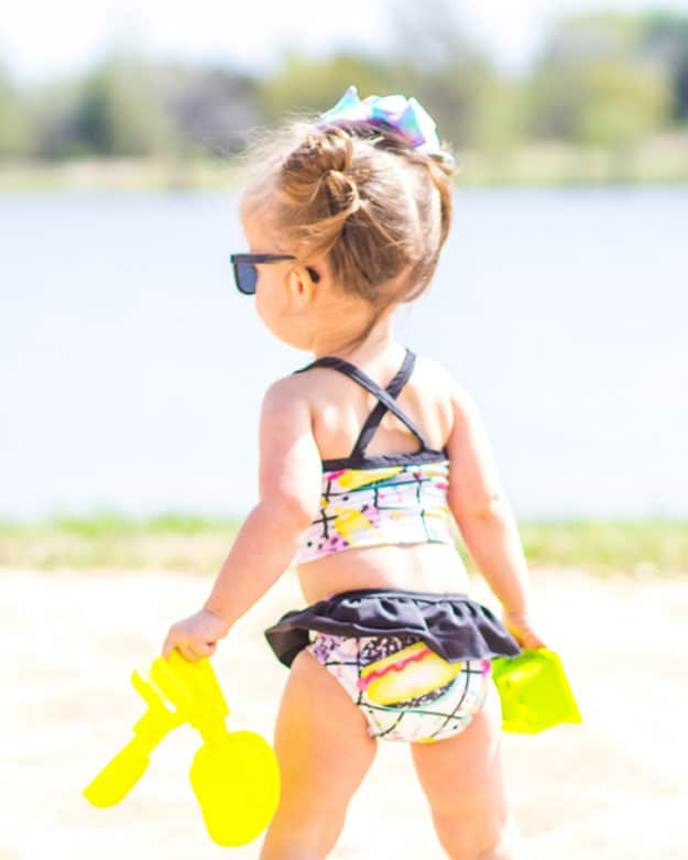 Simple life Pattern Company | Baby Marina's Criss Cross Tankini and One Piece. Downloadable PDF Sewing pattern for Baby sizes Newborn to 24 months. Baby Marina features the on-trend criss-cross strap in the back. It can be sewn as a one piece or a tankini. Both versions can feature the optional top ruffle or it can be made as a simple swimsuit without the ruffle. The tankini also has an optional skirt ruffle for the ultimate girly swimsuit. Fully lined or partial lining. A shorten/lengthen line is included for the perfect fit and coverage you may want. If you prefer a one piece for more sun coverage, an optional snap crotch panel is included for easy diaper changes.