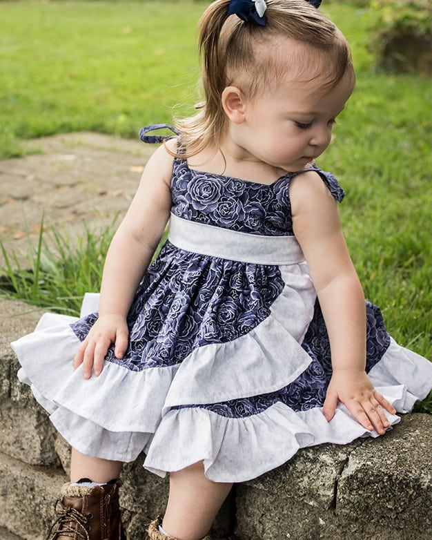Baby Opal's Wrap Skirt Top & Dress. Downloadable PDF Sewing Pattern for Baby Sizes Newborn to 24 Months. Baby Opal's Wrap Skirt Top & Dress is the sweetest sundress you'll own??  With two adorable necklines options, a slight sweetheart or adorable square neckline, Baby Opal is sure to be a favorite of yours and the little lady you are sewing for.  Baby Opal offers two skirt lengths: tunic and dress length.  The skirt has so many beautiful options, this pattern has something for everyone.  With a circle skirt or gathered skirt option you can create a simple skirt, a ruffled skirt, a simple wrap skirt or a fully ruffled wrap skirt.  Heading to a fancy affair?  Dress Opal up by adding the optional front sash and ties.  Not feeling fancy today?  Leave them off completely or add the sweet front bow for a more causal look.  The back bodice closes with buttons or snaps.  Baby Opal has delicate ties straps to finish this summer staple off with a sweet feminine look.